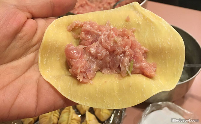 Hold a piece of the wrapper on your palm, scoop 2 tsp of pork mixture on the centre, and add a piece of shrimp bite on it.