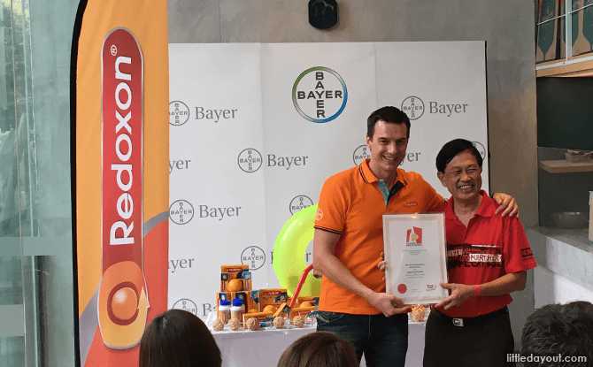 Ludovic Rassat, Country Division Head Singapore & South Asia Bayer Consumer Health, receives the certificate from Mr Ong, Singapore Book of Records, certifying that Boost & Slide is Singapore's longest street water slide.