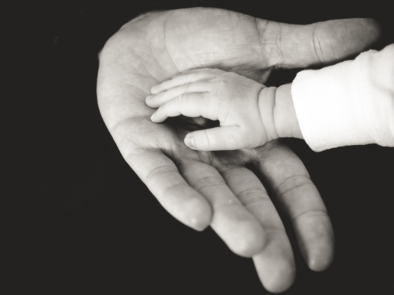 Father and baby touching hands