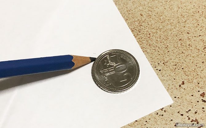 Take the 50 cent coin and trace two circles of that size and cut it out.