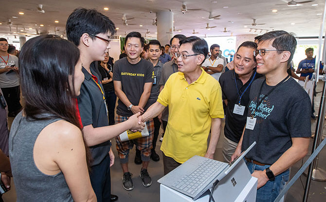 Code in the Community graduate Aiden McEwan presenting his project to DPM Heng Swee Keat.