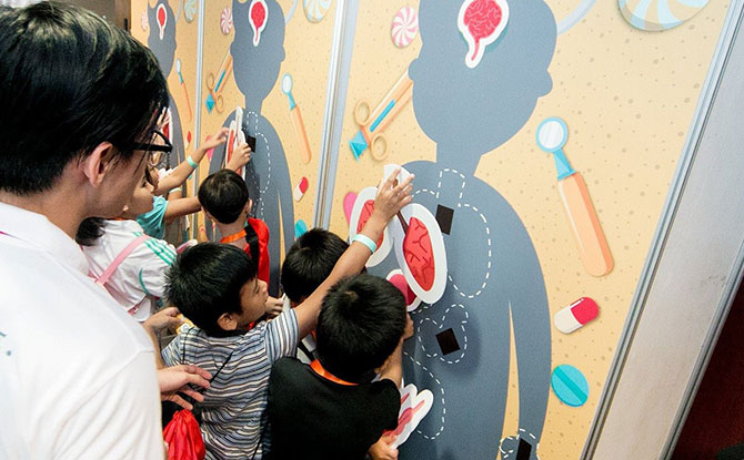 Little ones learn about body anatomy as they place the correct organs on life-sized body silhouettes.- Gleneagles Hospital Singapore 60th anniversary carnival