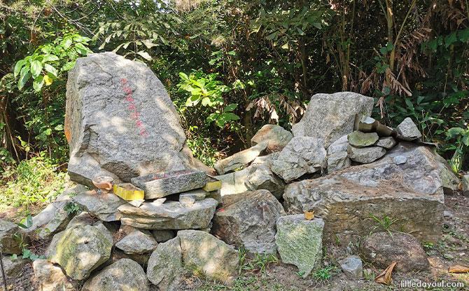 pile of rocks across the entrance of the little shrine