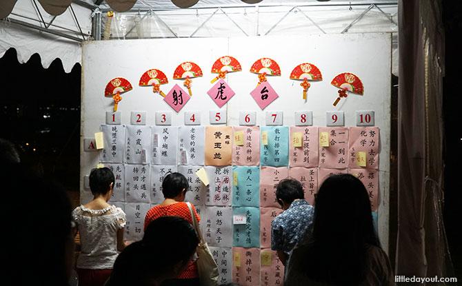 Visitors solving lantern riddles at Jurong Lake Gardens' Mid-Autumn Festival celebrations.