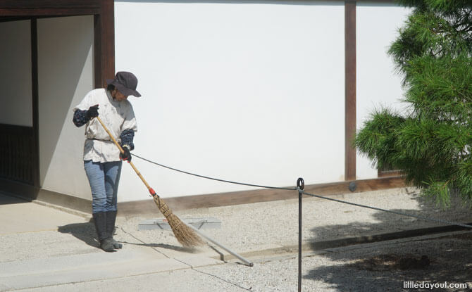 Staff cleaning the grounds of the Kyoto Imperial Palace.