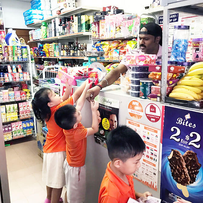 Children making real purchases at a nearby mama shop.
