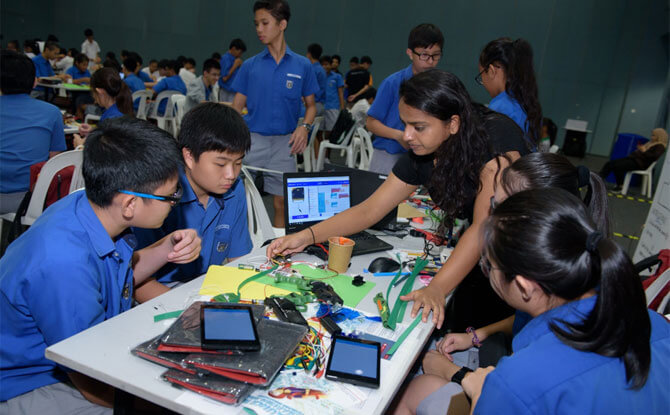 Nila Govindaraju, intern at Science Centre Singapore assisting fellow e-waste warriors as they apply their skills of coding and computational thinking. Nila designed the blended learning content and simplified the core robotic modules participants used during Caltex Fuel Your School - Tech Jam 2018.