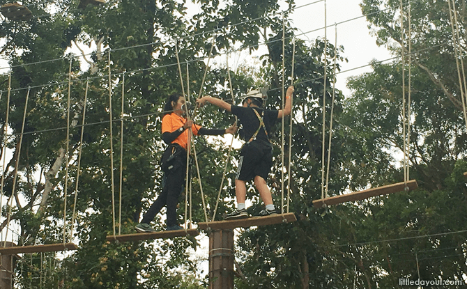 Instructor assisting a participant on the Forest Adventure rope course