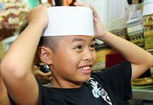 Malay boy with hands on head
