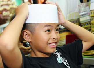 Malay boy with hands on head
