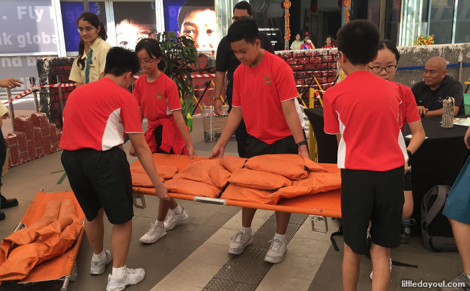 Using a stretcher at the SCDF Showcase, S'pore Discovery Centre