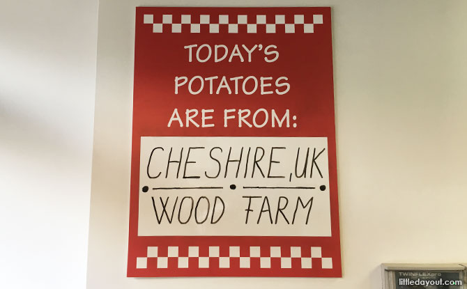 Sign at a Five Guys London outlet stating where the potatoes are sourced from.