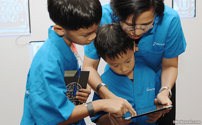 (Clockwise from left) Joshua Cheong, Samuel Cheong, and their mum Kimberly Quek work together to identify the patient's symptoms.