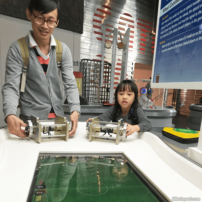 Father and daughter having scientific fun at the robotics gallery.