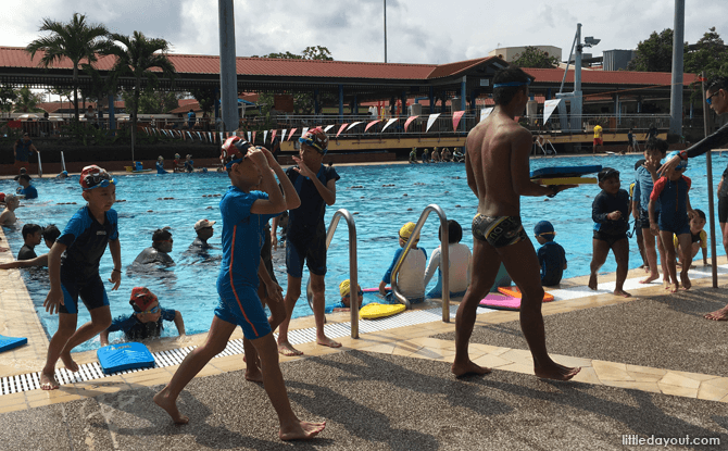 A crowded public pool with many swim classes going on at the same time