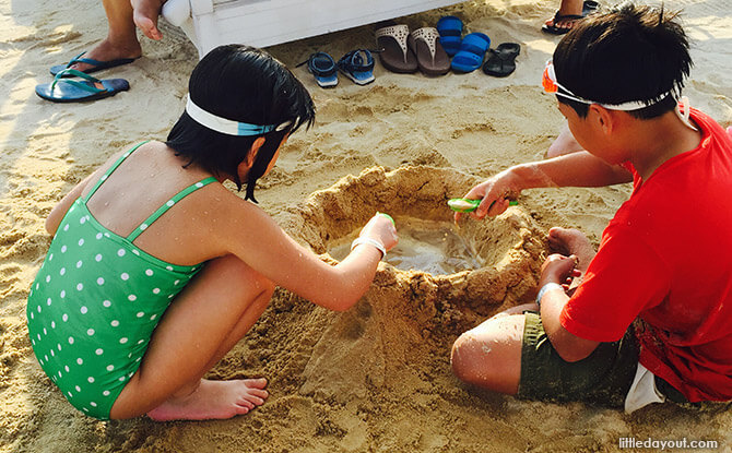 Kids playing with sand at The Canopi Resort, Bintan