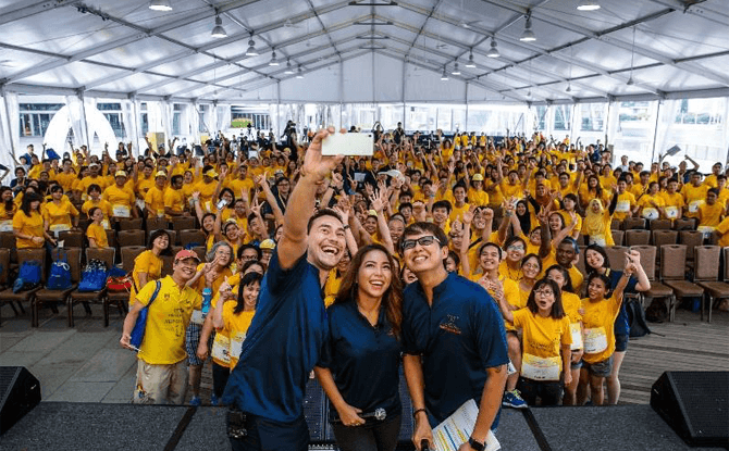 Emcees Paul Foster, Charmaine Yee and Glenn Ong gathering the crowd for a 'WeFie' at Play It Forward 2016